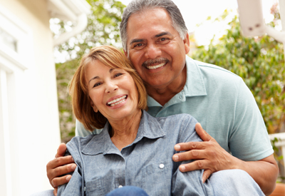 Hispanic couple smiling on porch