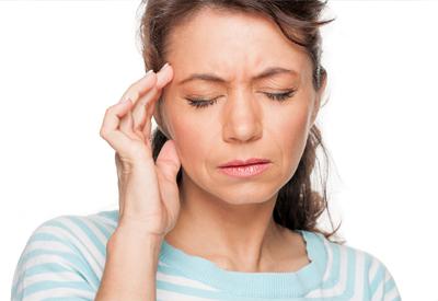 Woman rubbing head in pain