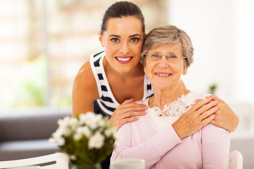 Woman and elderly woman smiling together