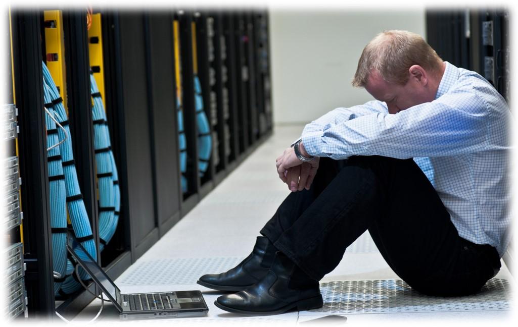 man looking down in server room